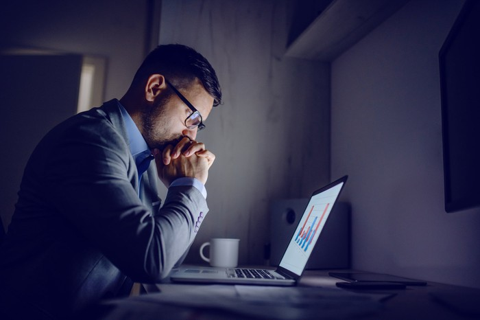 Serious person at laptop in dark room looking at laptop screen