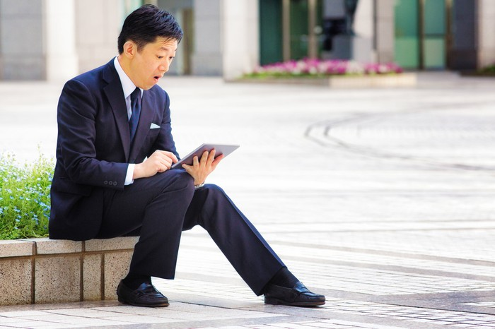 A man in a suit steps back in front of his tablet sitting outside.