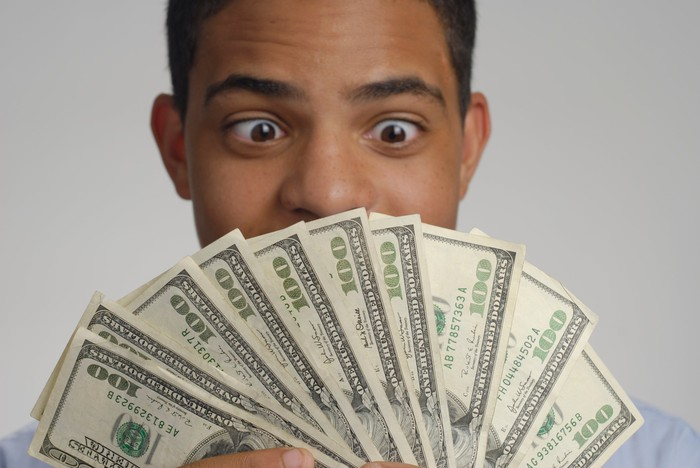 person holding $1000 cash