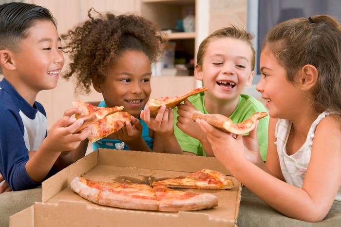 Four children eat pizza out of a box.