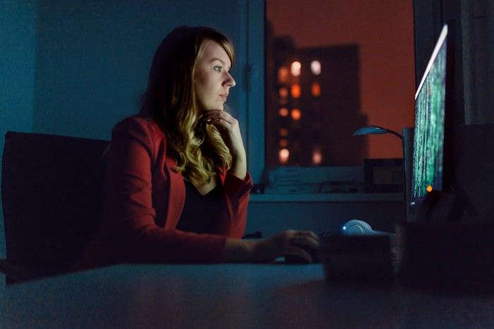 Person sitting at a desk in a dimly lit room works on code displayed on a PC.