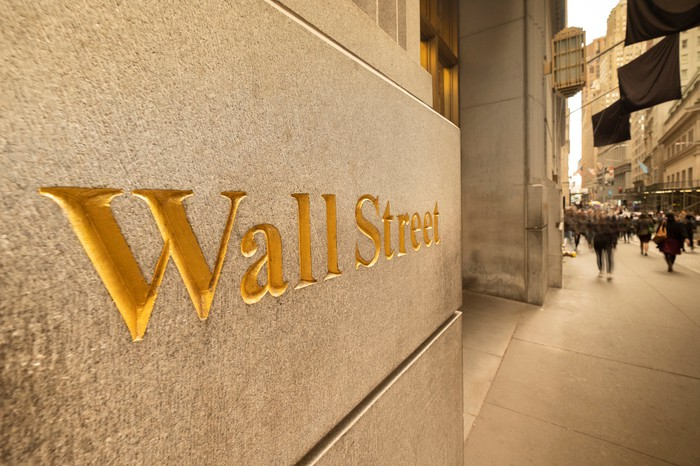 The words, Wall Street, etched in gold coloring on the side of a building.
