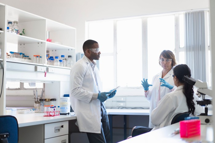 Three scientists standing in a laboratory bay work together to plan an experiment.