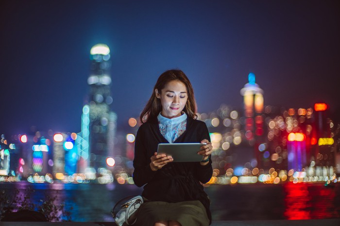 A person working from a tablet on front of a cityscape.