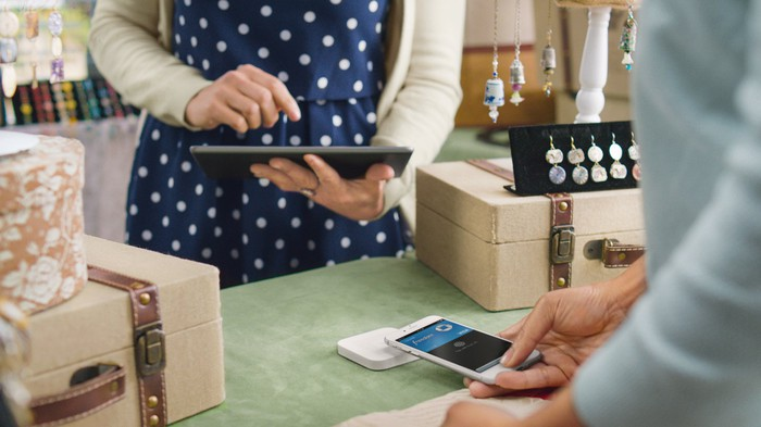 A shop assistant uses a Square reader to accept payment from a customer.