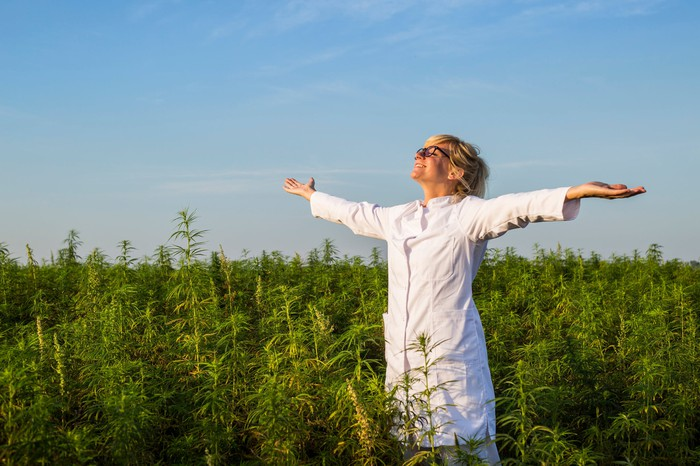 Cannabis farm technician holding arms extended out and smiling.