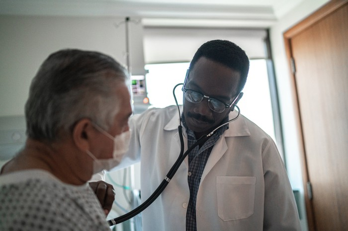 A doctor listening to a patient's heart using a stethoscope.