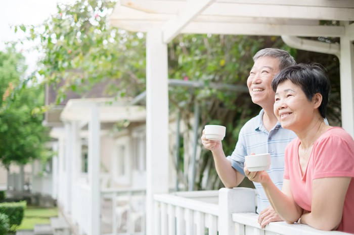 Senior couple smiling on their porch with coffee.