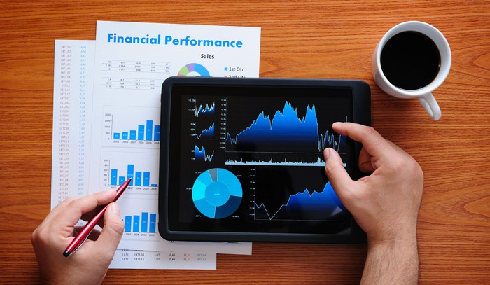 Investor reviewing financial charts, both on paper and with a tablet, while a full coffee cup sits on the side.