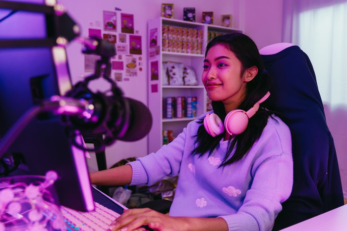 A gamer sits in front of a computer with an external microphone, for streaming.