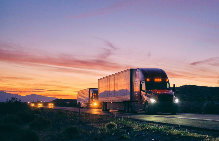 A semi truck hauls freight on an open highway at dusk.