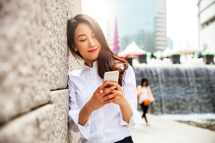 A smiling smartphone user in Seoul, South Korea.