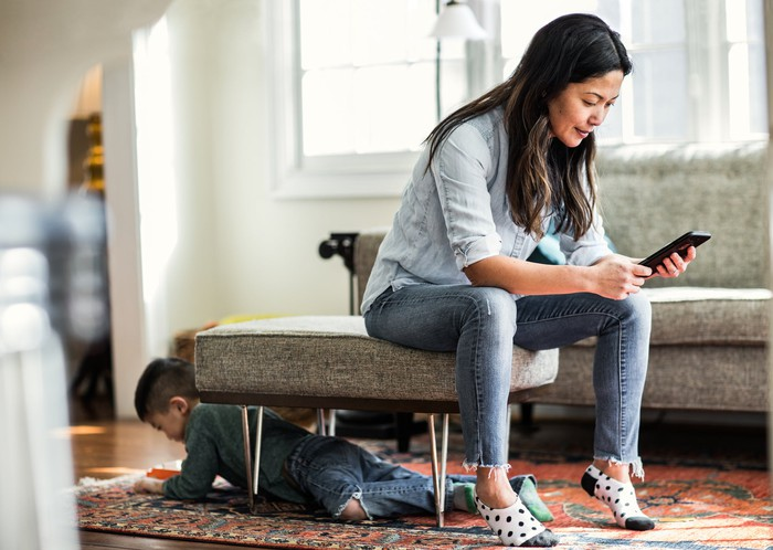 A mother and her son at home wearing jeans.