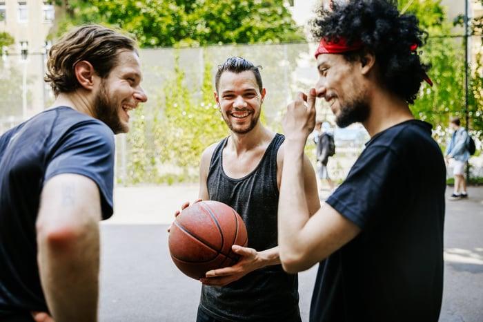 Three basketball players having fun at an outdoor basketball court.