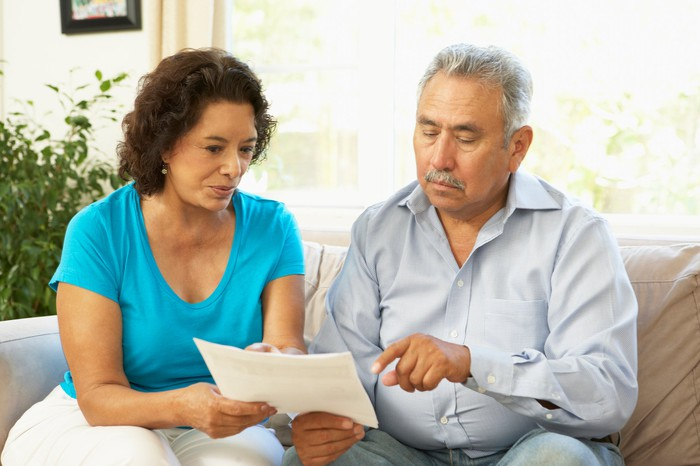 Two seniors looking at document.