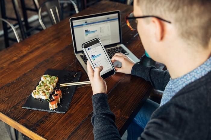 Investidor verificando ações em seu telefone.