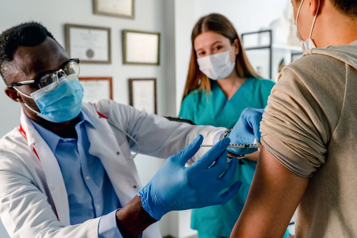 Healthcare professional giving a vaccine shot to a person with another healthcare professional watching.