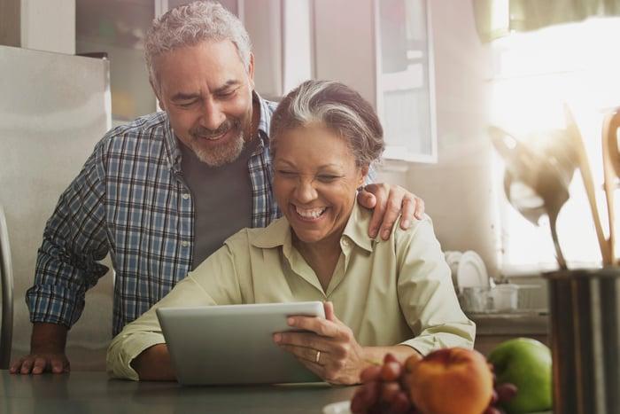 Deux personnes souriantes regardant une tablette.