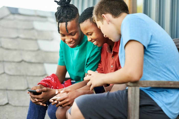 Three teens enjoying a mobile game while sitting on a bench outside.