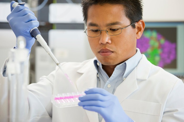 A lab technician using a pipette to fill a test tray with liquid.