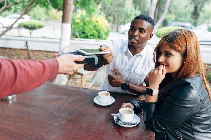 A couple drinking coffee, with one person using their smartphone to make a contactless payment.