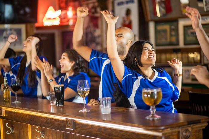Sports fans cheering in a bar.