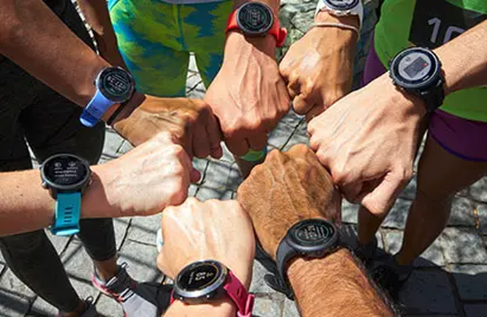 Seven hands in a circle showing Garmin watches.