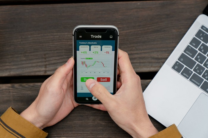 Person's hands hold a sell phone, on which an image of stock price movements, buy and sell buttons are displayed.