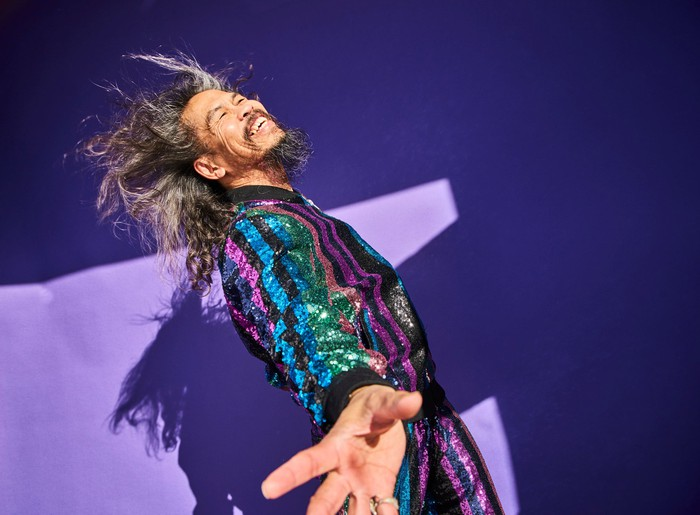 happy person in colorful disco outfit dancing against purple background