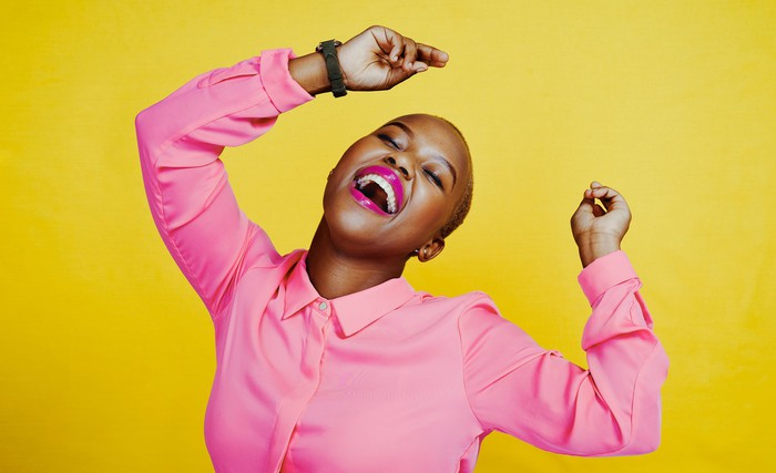 Happy person in bright pink shirt dancing and smiling against yellow background.