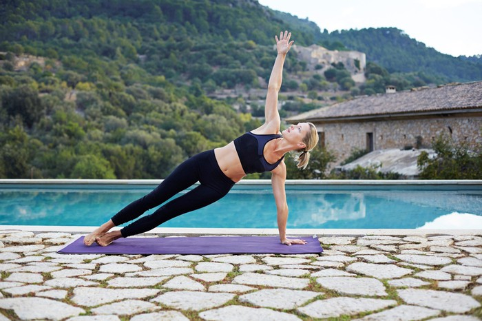 Middle-aged blond-haired woman in black athletic clothes doing yoga outside in front of a pool with mountains in background.