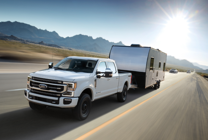 A Ford F-350 Super Duty pulling a trailer down a highway.