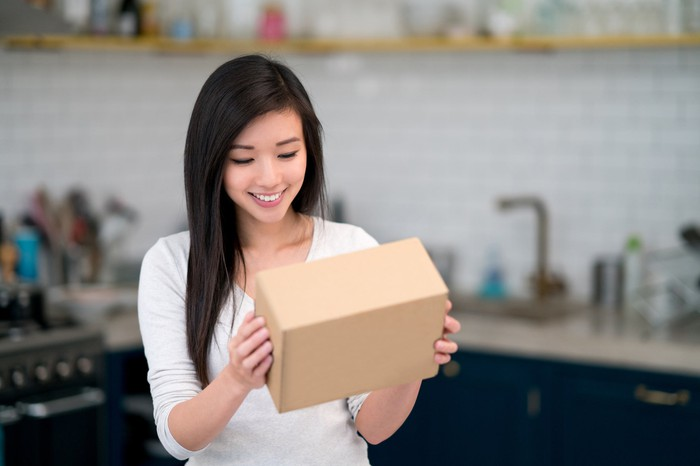 A woman holding a small, brown box.