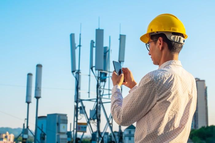 An engineer inspects a wireless tower.