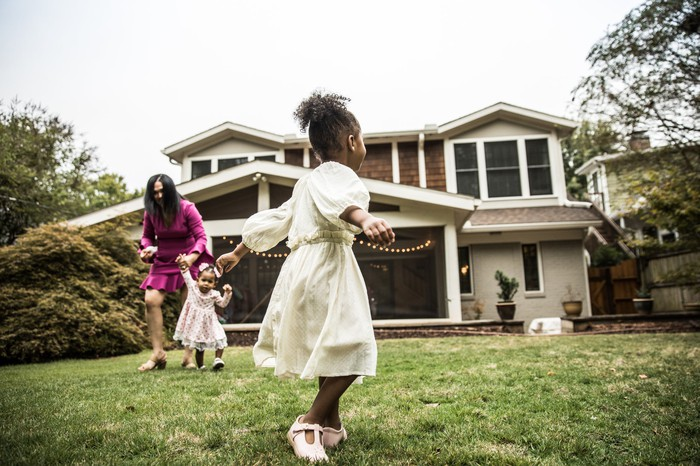 A young child twirling in front of a house with another child and adult on the lawn in the background.