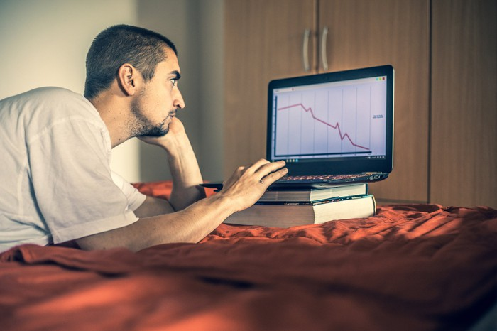 A man looks at a falling red line graph on a laptop.