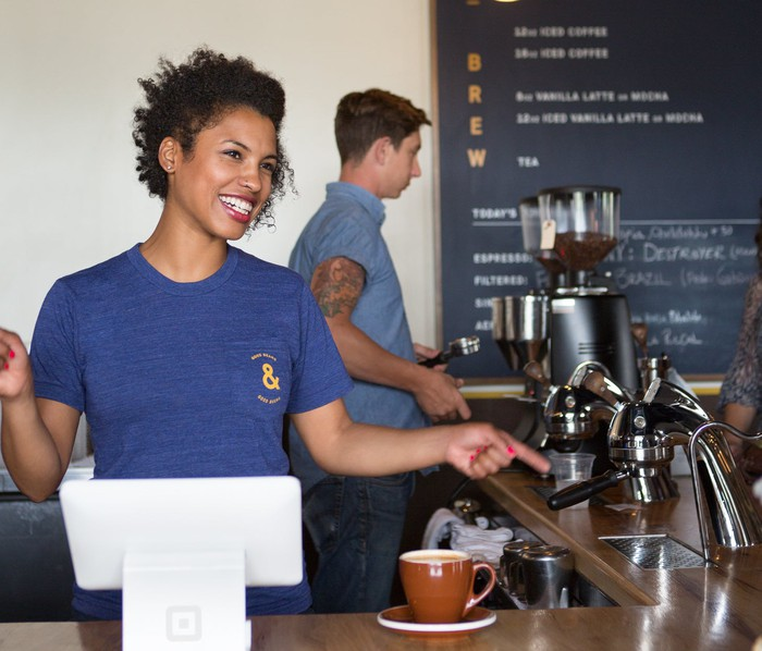 Barista at a coffee shop using Square hardware.