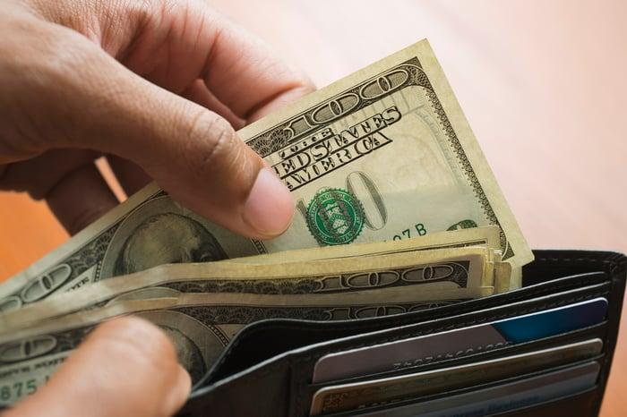 Une personne sort un billet de 100 $ de son portefeuille.