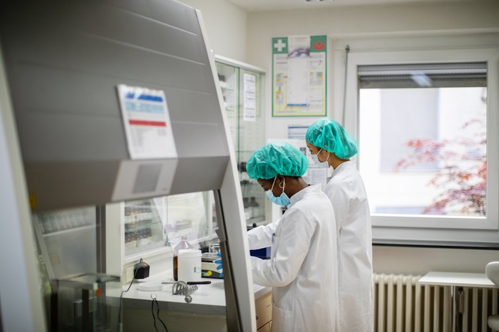 Two scientists wearing face masks and hairnets work side by side while standing in a laboratory.