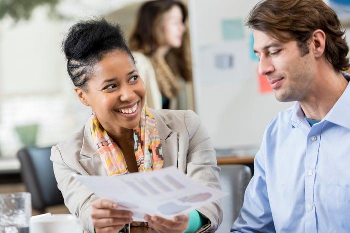 Un investisseur souriant montre une impression des données d'investissement à un autre tandis qu'un collègue se tient près d'un tableau blanc en arrière-plan.