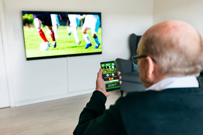 A person watching a soccer match on a large TV while making a bet on a mobile device.