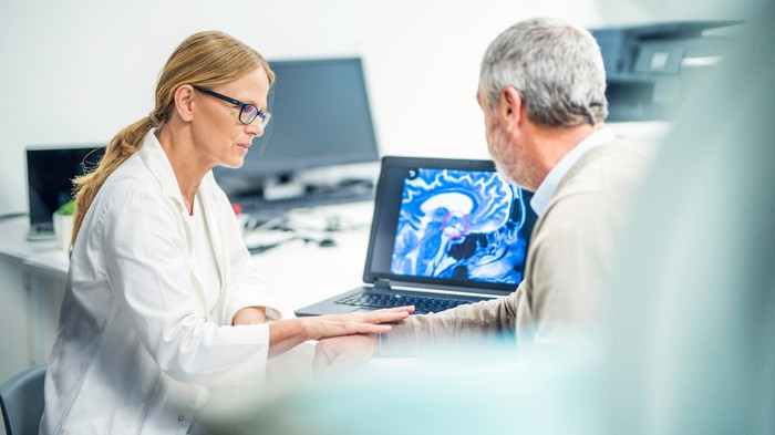 A medical professional shows an image of a brain scan on a laptop to another person while touching their arm.