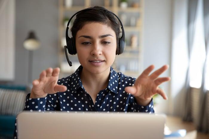Femme portant un casque faisant des gestes avec les mains sur un ordinateur portable