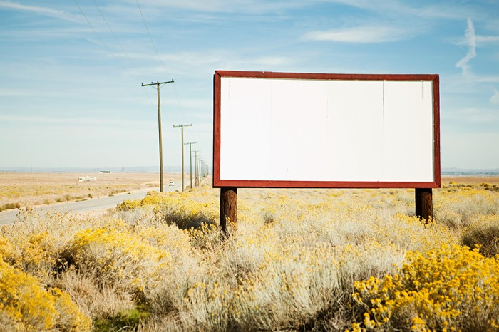 A blank  billboard on the side of a desert highway.