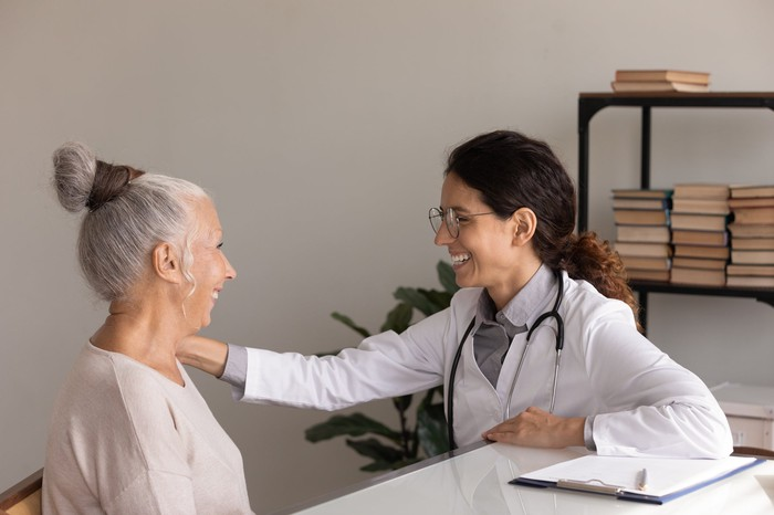 A doctor smiles while touching the arm of a smiling senior patient.
