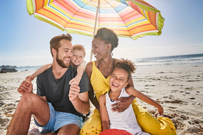 A family sits on a beach under a parasol as they enjoy a family vacation.