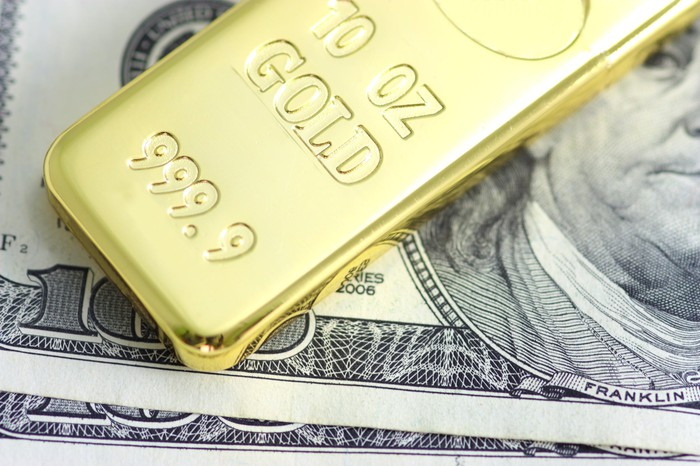 A gold bar rests on a one hundred dollar bill.
