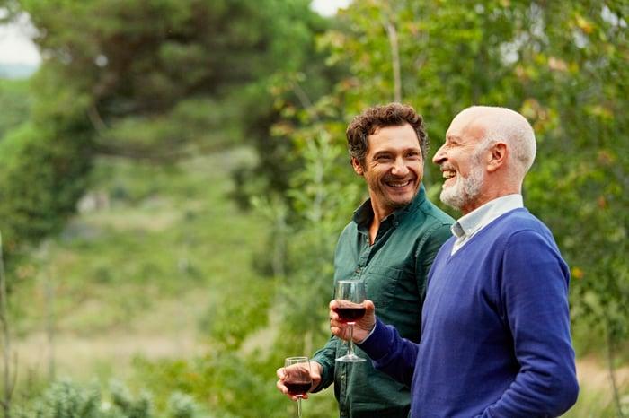 Deux personnes souriantes tenant des verres à vin à l'extérieur.
