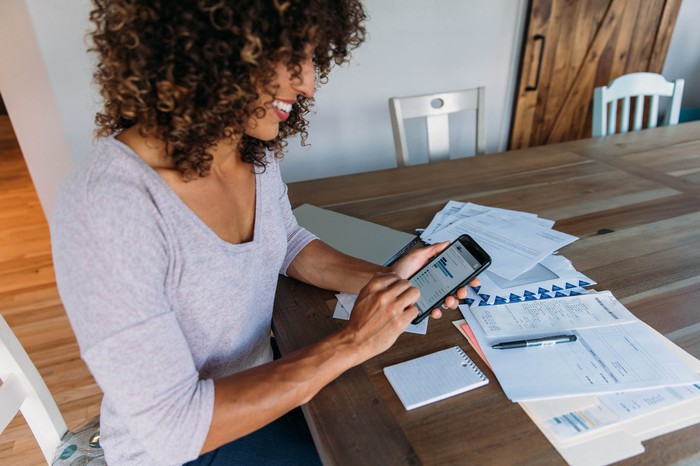 A woman enters financial data into her smartphone.