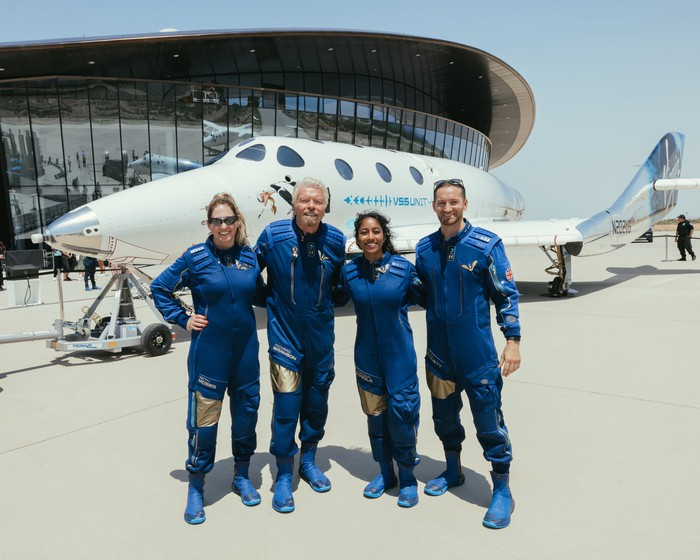 Four crew members from Unity 22 mission pose in front of the spacecraft.